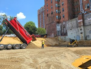 Truck dumping fill material on construction site